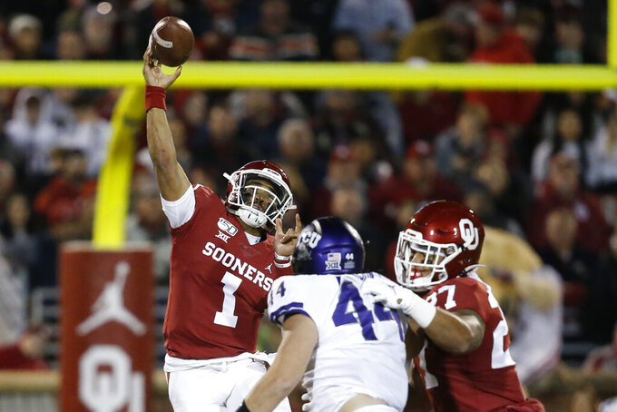 Oklahoma quarterback Jalen Hurts (1) passes under pressure from TCU defensive end Colt Ellison (44) in the first half of an NCAA college football game in Norman, Okla., Saturday, Nov. 23, 2019. (AP Photo/Sue Ogrocki)