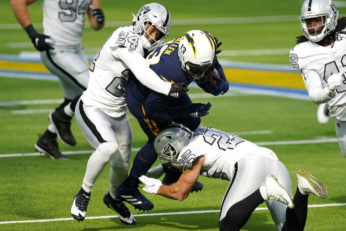 Los Angeles Chargers wide receiver Keenan Allen is brought down by Las Vegas Raiders strong safety Johnathan Abram (24) and free safety Erik Harris during the first half of an NFL football game Sunday, Nov. 8, 2020, in Inglewood, Calif. (AP Photo/Ashley Landis)