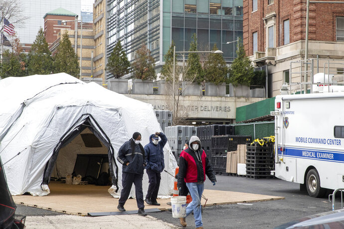 Medical Examiner personnel and construction workers are seen at the site of a makeshift morgue being built in New York, Wednesday, March 25, 2020. The number of people hospitalized with COVID-19 in New York climbed to 3,800, with close to 900 in intensive care, with the peak of the outbreak weeks away, Gov. Andrew Cuomo said Wednesday. The new coronavirus causes mild or moderate symptoms for most people, but for some, especially older adults and people with existing health problems, it can cause more severe illness or death. (AP Photo/Mary Altaffer)