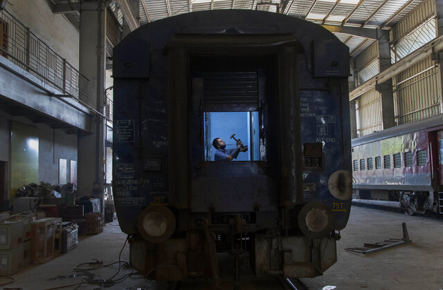 An Indian railway employee works to convert a train coach into an isolation ward for the fight against the new coronavirus in Gauhati, India, Sunday, March 29, 2020. Indian Prime Minister Narendra Modi apologized to the public on Sunday for imposing a three-week national lockdown, calling it harsh but