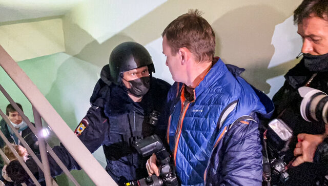 A police officer pushes photographers from a door of the apartment where Oleg Navalny, brother of jailed opposition leader Alexei Navalny lives in Moscow, Russia, Wednesday, Jan. 27, 2021. Police are searching the Moscow apartment of jailed Russian opposition leader Alexei Navalny, another apartment where his wife is living and two offices of his anti-corruption organization. Navalny's aides reported the Wednesday raids on social media. (AP Photo/Mstyslav Chernov)
