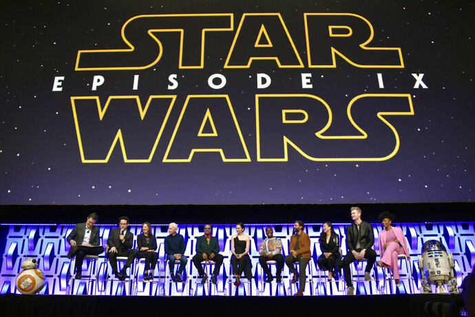FILE - In this April 12, 2019, file photo, Stephen Colbert, from left, J.J. Abrams, Kathleen Kennedy, Anthony Daniels, Billy Dee Williams, Daisy Ridley, John Boyega, Oscar Isaac, Kelly Marie Tran, Joonas Suotamo and Naomi Ackie participate in the