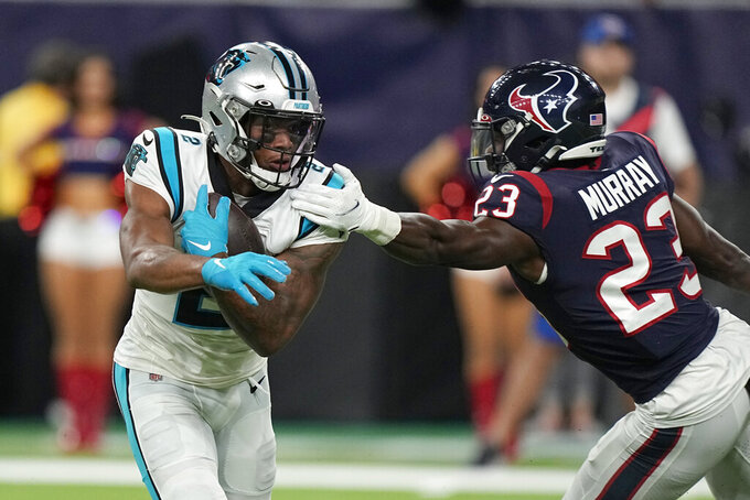 Houston Texans safety Eric Murray (23) reaches to tackle Carolina Panthers wide receiver DJ Moore (2) during the first half of an NFL football game Thursday, Sept. 23, 2021, in Houston. (AP Photo/Eric Christian Smith)