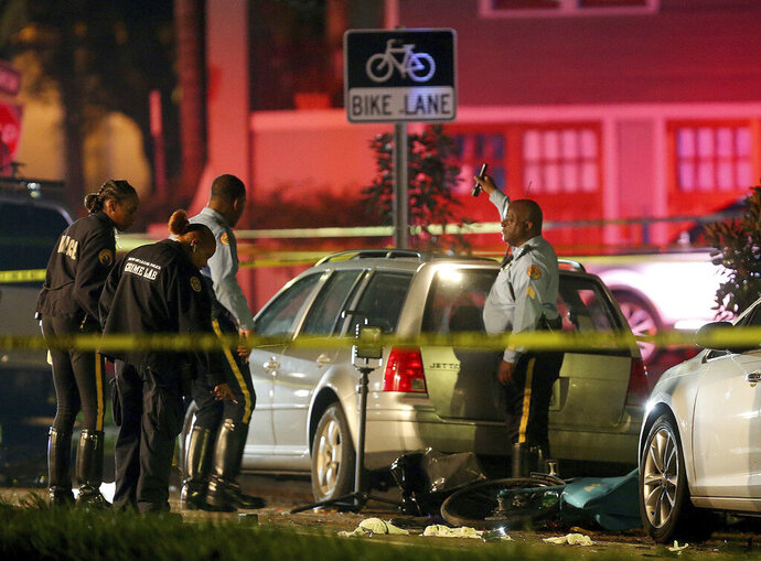 FILE - In this file photo, New Orleans Police examine damaged cars and bicycles on Esplanade Avenue in New Orleans after a car struck multiple people, killing several and injuring others following the Endymion Mardi Gras parade on Saturday, March 2, 2019. A man who drunkenly drove into a group of bicycle riders after the parade pleaded guilty Monday, Oct. 28 to two counts of vehicular homicide, averting a scheduled trial and opening himself for a possible 80-year prison sentence. (Michael DeMocker/The Times-Picayune/The New Orleans Advocate via AP, File)
