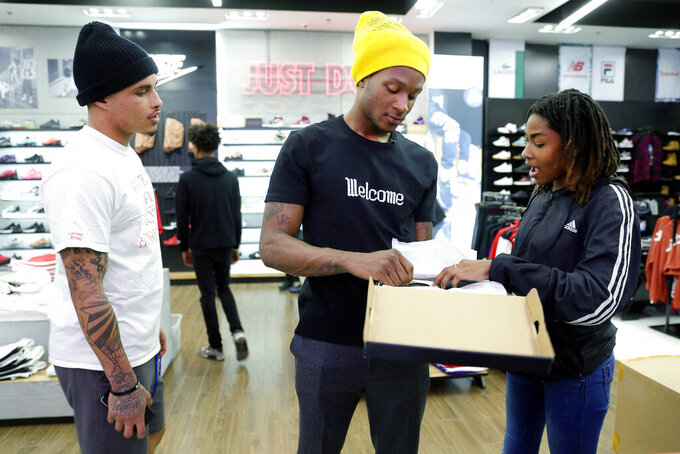 Houston Texans players Kenny Stills, left, and De'Andre Hopkins, center, comment on a pair of shoes chosen by Miracle Washington-Tribble at Shoe Palace during a shopping spree Monday, Dec. 16, 2019, at Galleria Mall in Houston. Washington-Tribble is one of two teens that day who are beneficiaries of Eight Million Stories, a Houston program which helps 14-18-year-olds who have either quit or been kicked out of school continue their education, find employment and receive emotional support. (AP Photo/Michael Wyke)