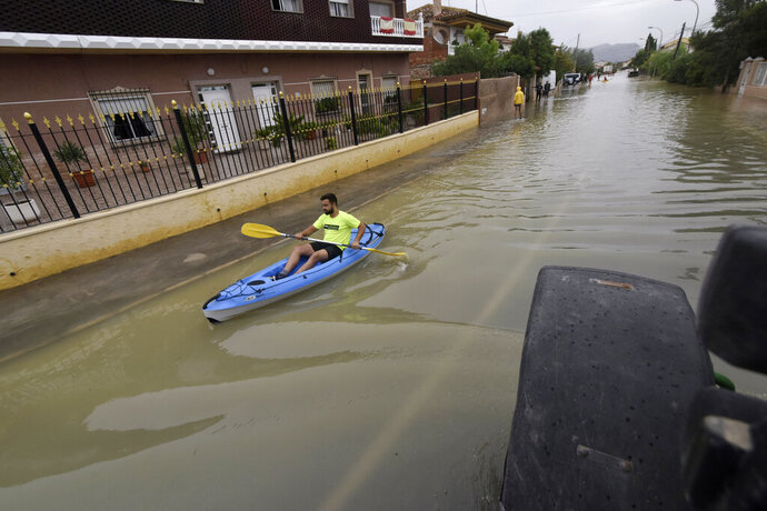 A man uses a canoe along a flooded road after heavy raining in El Raal, near Murcia, Spain, Saturday, Sept. 14, 2019. Authorities say that record rainfall in southeastern Spain have claimed the lives of two more victims, taking the death toll to six from the storms that have flooded roads and towns. A sixth victim was confirmed by authorities on Saturday, a 41-year-old man in the town of Orihuela, where the river Segura overflowed its banks on Friday. (AP Photo/Alfonso Duran)