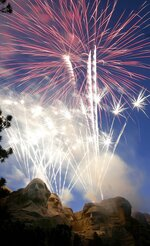 FILE - Fireworks light up the night sky over Mt. Rushmore National Memorial, S.D on Tuesday, July 3, 2007. When President Donald Trump speaks at the Mount Rushmore national memorial Friday, July 3, 2020, before the first fireworks show there in years, he'll stand before a crowd of thousands of people who won't be required to socially distance or wear masks despite the coronavirus pandemic. Public health experts say the lack of social distancing and enforced mask-wearing could lead to a surge in the disease, while the fireworks risk setting the surrounding forest ablaze. ( Seth A. McConnell/Rapid City Journal via AP, File)