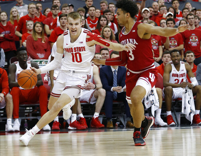 Ohio State's Justin Ahrens, left, dribbles past Indiana's Justin Smith during the second half of an NCAA college basketball game Saturday, Feb. 1, 2020, in Columbus, Ohio. Ohio State beat Indiana 68-59. (AP Photo/Jay LaPrete)