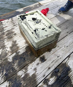 In this May 9, 2020, photo provided by Catherine Brewer, is a safe that Knox Brewer pulled out of Whitney Lake in South Carolina. The 6-year-old was using a magnet attached to a string to fish for metal in the water when he reeled in a lockbox that police said was stolen from a woman who lived nearby eight years ago. (Catherine Brewer via AP)