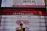 A man wearing a face mask walks past a bank's electronic board showing the Hong Kong share index at Hong Kong Stock Exchange in Hong Kong Monday, April 19, 2021. Asian shares were mixed Monday amid cautious optimism about a global rebound from the coronavirus pandemic. (AP Photo/Vincent Yu)