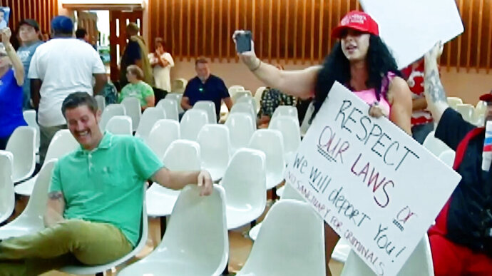 This photo from video provided by KVOA-TV shows Alex Kack, in the green shirt at left, laughing at a protester during a vote to put a