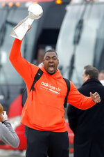 Kansas City Chiefs defensive tackle Chris Jones reacts as he holds up the Vince Lombardi Trophy, as he and his teammates return home a day after winning the NFL Super Bowl 54 football game Monday, Feb. 3, 2020, in Kansas City, Mo. The Chiefs defeated the San Francisco 49ers 31-20, to win their first championship in 50 years. (AP Photo/Colin E. Braley)
