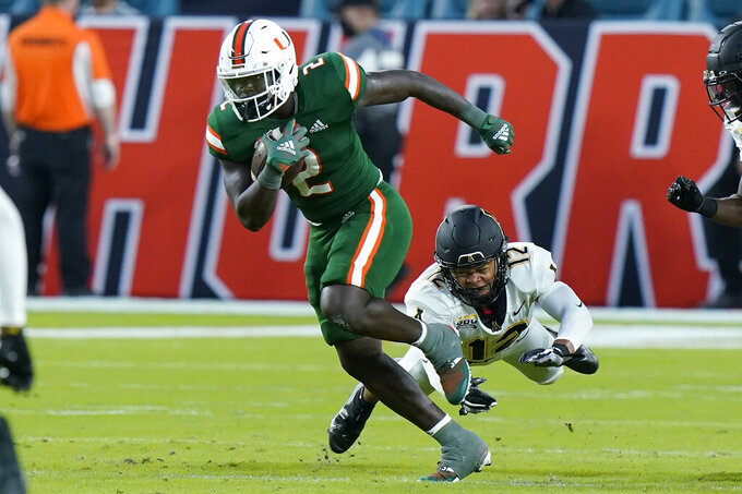 Miami running back Donald Chaney Jr. (2) avoids a tackle by Appalachian State defensive back Madison Cone (12) during the first half of an NCAA college football game, Saturday, Sept. 11, 2021, in Miami Gardens, Fla. (AP Photo/Wilfredo Lee)