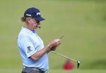 Miguel Jimenez checks his yardage book on the 1st green during a practice round ahead of the start of the British Open golf championships at Royal Portrush in Northern Ireland, Tuesday, July 16, 2019. The British Open starts Thursday. (AP Photo/Peter Morrison)
