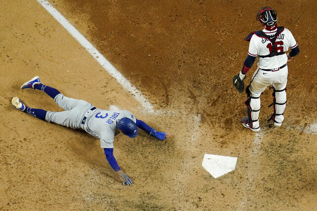 Los Angeles Dodgers' Chris Taylor scores past Atlanta Braves catcher Travis d'Arnaud on a hit by Mookie Betts during the seventh inning in Game 5 of a baseball National League Championship Series Friday, Oct. 16, 2020, in Arlington, Texas. (AP Photo/David J. Phillip)
