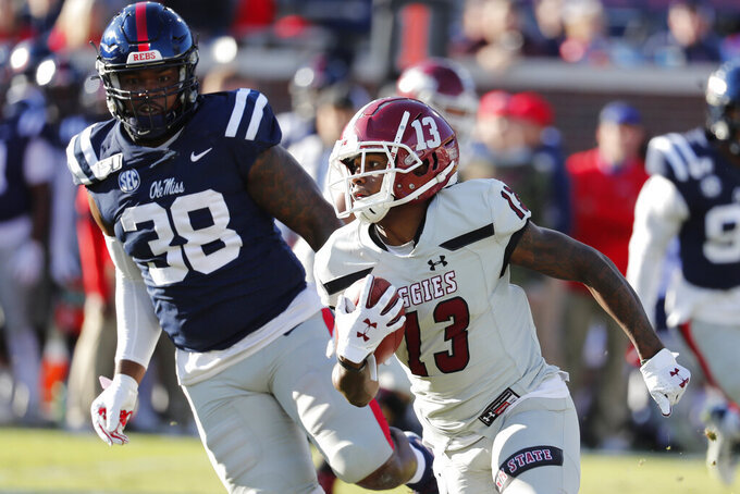 New Mexico State wide receiver Tony Nicholson (13) runs past Mississippi defensive end Austrian Robinson (38) with a pass reception for short yardage during the first half of an NCAA college football game in Oxford, Miss., Saturday, Nov. 9, 2019. (AP Photo/Rogelio V. Solis)