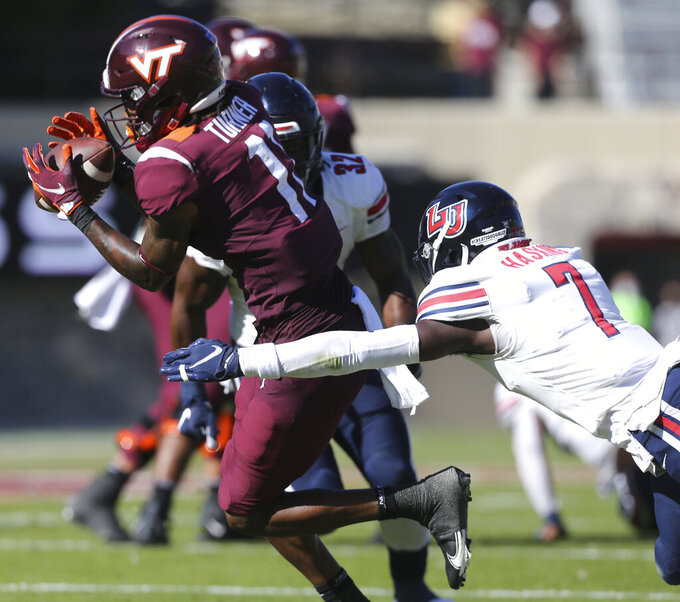Virginia Tech's Tré Turner, left, catches a pass as Liberty's Marcus Haskins closes in during the first half of an NCAA college football game, Saturday, Nov. 7 2020, in Blacksburg, Va. (Matt Gentry/The Roanoke Times via AP, Pool)