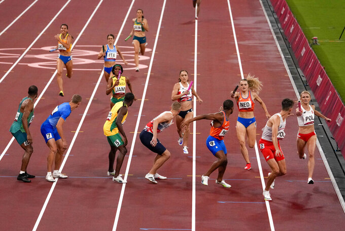 Runners compete in a heat of the 4 x 400-meter mixed relay at the 2020 Summer Olympics, Friday, July 30, 2021, in Tokyo. (AP Photo/Charlie Riedel)