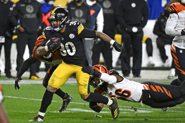 Pittsburgh Steelers running back James Conner (30) gets past Cincinnati Bengals middle linebacker Josh Bynes (56) during the second half of an NFL football game in Pittsburgh, Sunday, Nov. 15, 2020. (AP Photo/Don Wright)