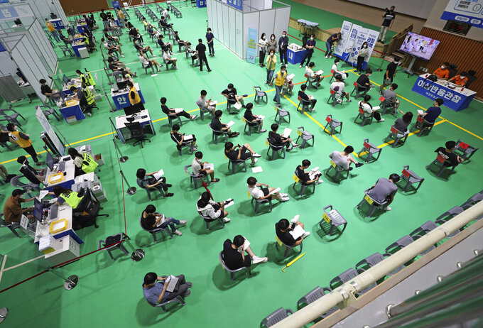 High school seniors and faculty members wait to be monitored for possible side effects after receiving the first dose of the Pfizer-BioNTech COVID-19 coronavirus vaccine at a vaccination center in Daegu, South Korea, Monday, July 19, 2021.(Kim Jun-beom/Yonhap via AP)