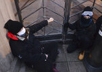 A woman is handcuffed to the gate in front of the Education Ministry building in Warsaw, Poland, on Monday Nov. 23, 2020. Police detained several people as women-led protests over abortion rights flared up again in Warsaw and elsewhere in Poland. The protests, organized by the group Women's Strike, have been occurring regularly ever since the country's constitutional court issued an Oct. 22 ruling that further tightens an abortion law that was already one of the most restrictive in Poland.(AP Photo/Czarek Sokolowski)