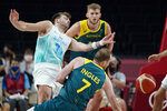 Slovenia's Luka Doncic (77) is fouled by Australia's Joe Ingles (7) during the men's bronze medal basketball game at the 2020 Summer Olympics, Saturday, Aug. 7, 2021, in Tokyo, Japan. (AP Photo/Charlie Neibergall)