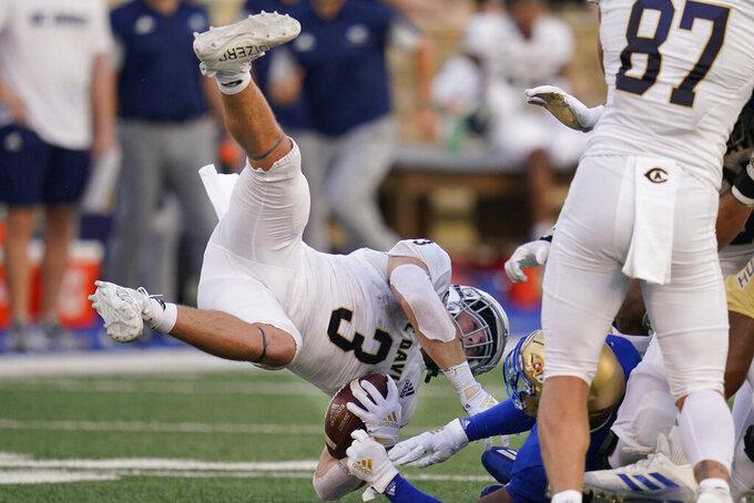 UC Davis running back Lan Larison (3) falls after a hit from Tulsa cornerback Tyon Davis, right, during the first half of an NCAA college football game Thursday, Sept. 2, 2021, in Tulsa, Okla. (AP Photo/Sue Ogrocki)