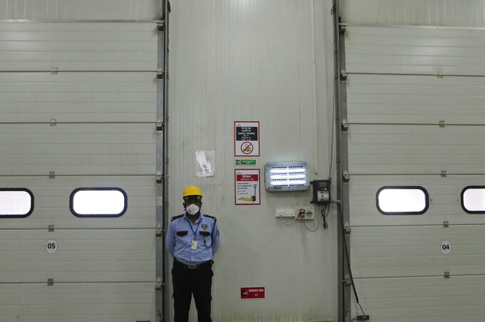 A security guard stands by at Snowman Logistics, India's largest cold storage company in Taloja on the outskirts of Mumbai, India, Saturday, Oct. 17, 2020. The vaccine cold chain hurdle is just the latest disparity of the pandemic weighted against the poor, who more often live and work in crowded conditions that allow the virus to spread, have little access to medical oxygen vital to COVID-19 treatment, and whose health systems lack labs, supplies or technicians to carry out large-scale testing. (AP Photo/Rajanish Kakade)