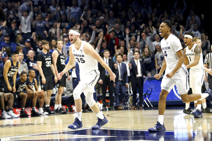 Xavier forward Zach Hankins (35), guard Elias Harden (4) and guard Paul Scruggs (1) celebrate their victory after an NCAA college basketball game against Butler, Sunday, Jan. 13, 2019, in Cincinnati. (Kareem Elgazzar/The Cincinnati Enquirer via AP)