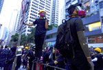 """Protesters gather in Central, the main business district in Hong Kong, Sunday, Sept. 8, 2019.  Thousands of demonstrators in Hong Kong urge President Donald Trump to """"liberate"""" the semi-autonomous Chinese territory during a peaceful march to the U.S. consulate, but violence broke out later in the business and retail district after protesters vandalized subway stations, set fires and blocked traffic. (AP Photo/Vincent Yu)"""