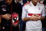 FILE - In this Feb. 9, 2015 file photo, an Ultras Al-Ahly soccer fan, left, and an Ultras White Knights soccer fan, pray for people who were killed in a riot outside a stadium, at Cairo University in Egypt. Egypt's close relations with Saudi Arabia are being tested by a soccer spat sparked by an uproar over meddling by the kingdom's sports minster, Turki al-Sheikh. The ongoing upheaval is destabilizing soccer in Egypt as it tries to shake off memories of the national team's group-stage exist at the World Cup in June and the deaths of nearly 100 fans this decade. (AP Photo/Roger Anis, El Shorouk Newspaper, File)