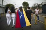 People walk to the Venezuela Aid Live concert that will play on the Colombian side of the border, in Urena, Venezuela, Friday, Feb. 22, 2019. Venezuela's power struggle is set to convert into a battle of the bands Friday when musicians demanding Nicolas Maduro allow in humanitarian aid and those supporting the embattled leader's refusal sing in rival concerts being held at both sides of a border bridge where tons of donated food and medicine are being stored. (AP Photo/Rodrigo Abd)