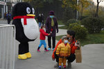 Adults look after children near a mascot for Tencent, a giant gaming platform in Beijing, China on Nov. 11, 2020. Hugely popular online games and celebrity culture are the latest targets in the ruling Communist Party's campaign to encourage China's public to align their lives with its political and economic goals. (AP Photo/Ng Han Guan)