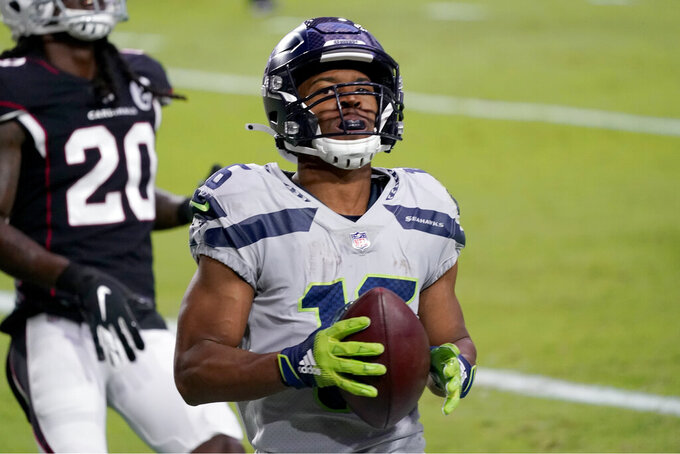 Seattle Seahawks wide receiver Tyler Lockett scores a touchdown as Arizona Cardinals cornerback Dre Kirkpatrick (20) defends during the first half of an NFL football game, Sunday, Oct. 25, 2020, in Glendale, Ariz. (AP Photo/Ross D. Franklin)