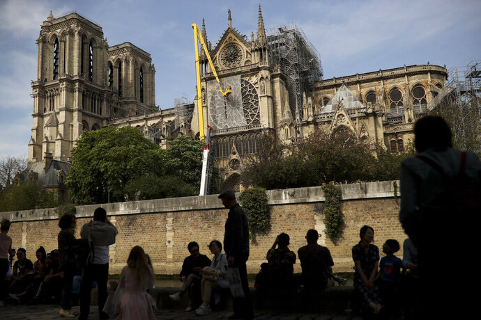 Workers, top, fix a net to cover one of the iconic stained glass windows of the Notre Dame Cathedral in Paris, Sunday, April 21, 2019. The fire that engulfed Notre Dame during Holy Week forced worshippers to find other places to attend Easter services, and the Paris diocese invited them to join Sunday's Mass at the grandiose Saint-Eustache Church on the Right Bank of the Seine River. (AP Photo/Francisco Seco)