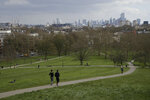 People jog down up Primrose Hill, with a backdrop of central London, as the lockdown due to the coronavirus outbreak continues in London, Tuesday, March 31, 2020. The British government advises people must try to stay at home to help stop the spread of coronavirus, they are allowed one form of exercise a day, such as a run, walk, or cycle, alone or with members of their household. The new coronavirus causes mild or moderate symptoms for most people, but for some, especially older adults and people with existing health problems, it can cause more severe illness or death. (AP Photo/Matt Dunham)