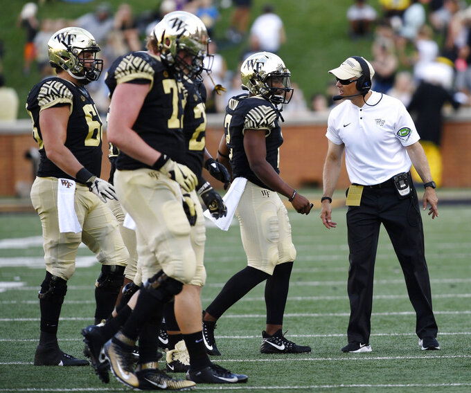 Wake Forest's head football coach Dave Clawson talks to his quarterback Kendall Hinton (2) as Hinton comes off the field during the second half of their NCAA college football game against Rice, Saturday, Sept. 29, 2018, in Winston-Salem, N.C. (AP Photo/Woody Marshall)