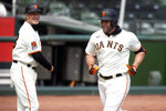 San Francisco Giants' Darin Ruf, right, runs out his solo home run during the second inning of a baseball game against the Seattle Mariners, Thursday, Sept. 17, 2020 in San Francisco. Third base coach Ron Wotus looks on. (AP Photo/D. Ross Cameron)