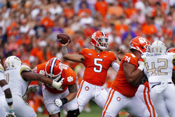 Clemson quarterback D.J. Uiagalelei (5) throws from the pocket as offensive linemen Matt Bockhorst (65) and Marcus Tate (74) block during the first half of an NCAA college football game against Georgia Tech, Saturday, Sept. 18, 2021, in Clemson, S.C. (AP Photo/John Bazemore)
