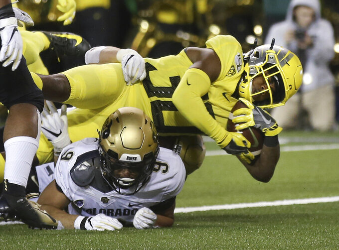 Oregon's Jaylon Redd, top, dives into the end zone for a touchdown over Colorado's Aaron Maddox during the second quarter of an NCAA college football game Friday, Oct. 11, 2019, in Eugene, Ore. (AP Photo/Chris Pietsch)