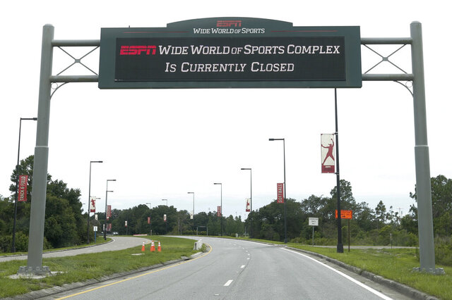 A sign at the entrance to ESPN's Wide World of Sports at Walt Disney World is seen Wednesday, June 3, 2020, in Kissimmee, Fla. The NBA has told the National Basketball Players Association that it will present a 22-team plan for restarting the season at Disney. (AP Photo/John Raoux)
