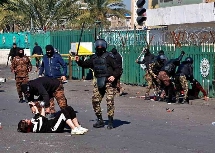 A riot policeman pins down a female anti-government protester to search her while security forces try to disperse demonstrators during clashes in Baghdad, Iraq, Monday, Jan. 27, 2020. (AP Photo/Khalid Mohammed)