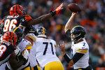 Pittsburgh Steelers quarterback Mason Rudolph (2) passes against Cincinnati Bengals defensive end Carlos Dunlap (96) during the first half an NFL football game, Sunday, Nov. 24, 2019, in Cincinnati. (AP Photo/Gary Landers)