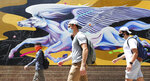 Students walk past a Pegasus mural at the Student Union at the University of Central Florida, in Orlando, Monday, August 24, 2020, on the first day of classes with new safety protocols in place to fight the coronavirus pandemic. (Joe Burbank/Orlando Sentinel via AP)