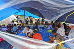 People who are displaced by an earthquake sit under in a makeshift tent at a temporary shelter in Mamuju, West Sulawesi, Indonesia, Sunday, Jan. 17, 2021. Rescuers retrieved more bodies from the rubble of homes and buildings toppled by the magnitude 6.2 earthquake while military engineers managed to reopen ruptured roads to clear access for relief goods. (AP Photo/Joshua Marunduh)
