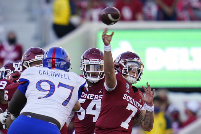 Oklahoma quarterback Spencer Rattler (7) throws under pressure from Kansas defensive lineman Kenean Caldwell (97) in the first half of an NCAA college football game in Norman, Okla., Saturday, Nov. 7, 2020. (AP Photo/Sue Ogrocki)