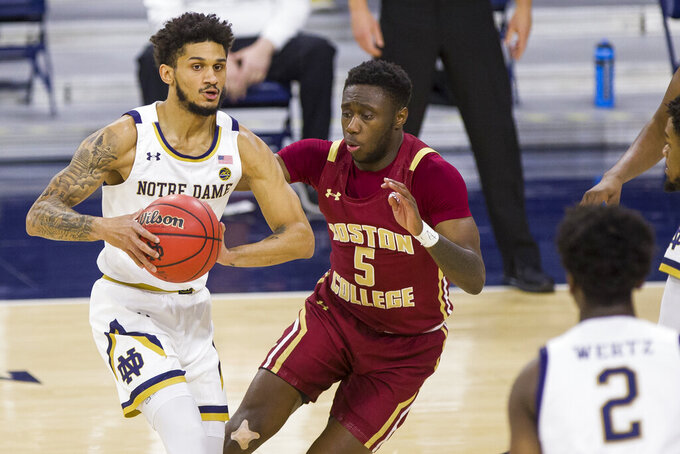 Notre Dame's Prentiss Hubb, left, looks to pass around Boston College's Jay Heath (5) during the first half of an NCAA college basketball game Saturday, Jan. 16, 2021, in South Bend, Ind. (AP Photo/Robert Franklin)