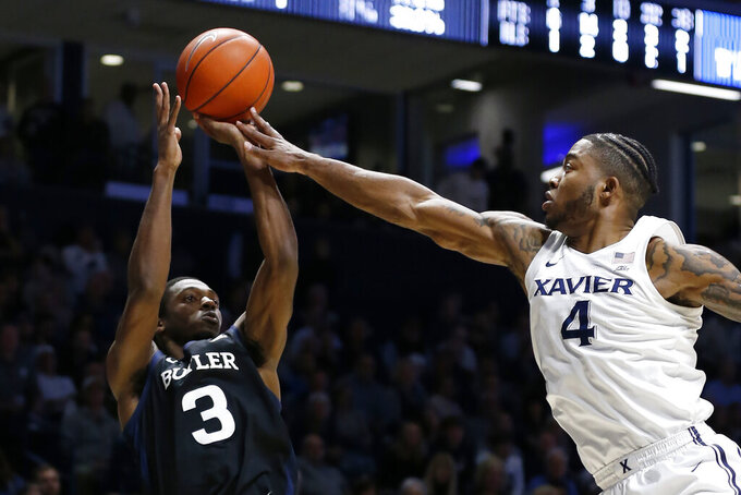 Butler guard Kamar Baldwin (3) shoots against Xavier forward Tyrique Jones (4) during the second half of an NCAA college basketball game Saturday, March 7, 2020, in Cincinnati. (AP Photo/Gary Landers)
