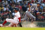 Boston Red Sox's Mookie Betts, left, scores on a two-run double by Andrew Benintendi as the ball gets by Toronto Blue Jays' Luke Maile during the second inning of a baseball game in Boston, Saturday, June 22, 2019. (AP Photo/Michael Dwyer)
