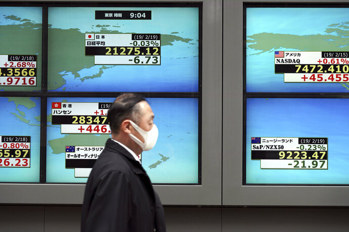 A man walks past an electronic stock board showing Japan's Nikkei 225 index and other country's index at a securities firm in Tokyo Tuesday, Feb. 19, 2019. Asian shares are mostly higher as Chinese and U.S. officials prepare for trade talks in Washington this week. (AP Photo/Eugene Hoshiko)